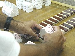 Hand-assembled paper covers are slipped over each cake of rosin.