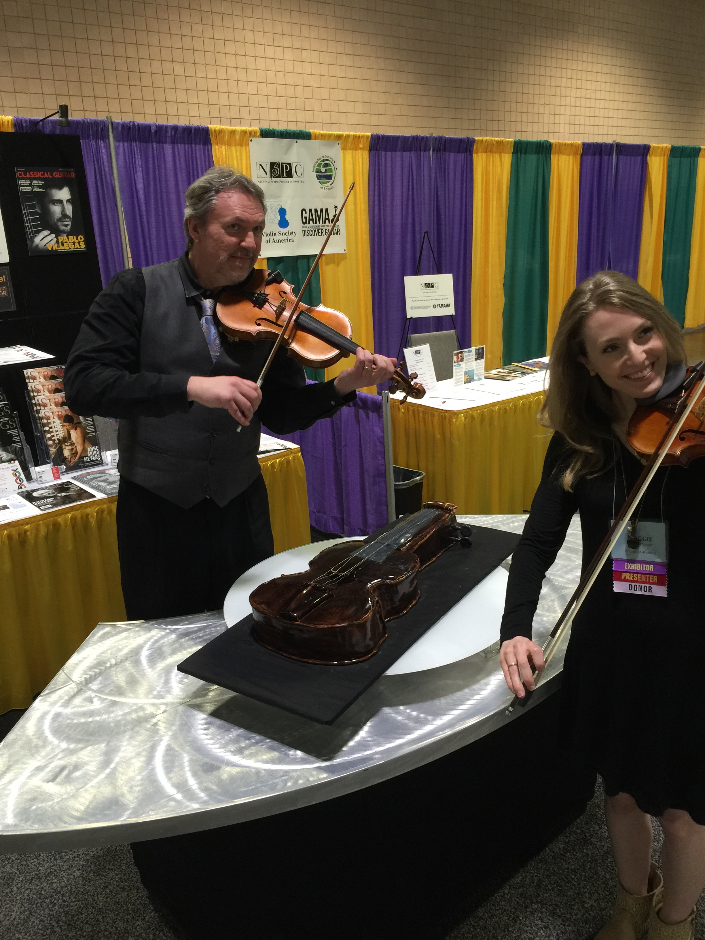 Mark and Maggie O'Connor fiddling around the violin cake.