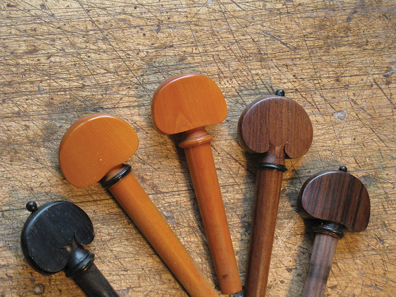 An array of pegs in various colors and wood such as snakewood, boxwood, and rosewood